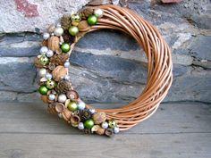Zelenkavý Vánoční proutěný věneček je ozdobenýšiškami, ořechy akouličkami v různých odstínech zelené a stříbrné barvy. Na dveře i do interieru. Věneček má průměr přibližně 27 cm.