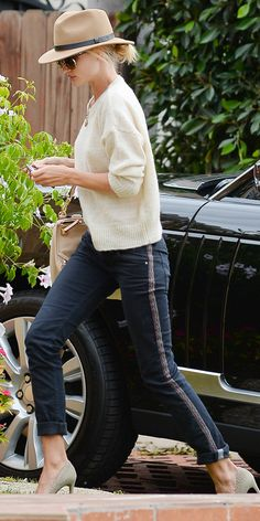 Rosie Huntington-Whiteley in a knit sweater, jeans with an embroidered panel, and heels