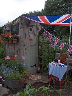 """Union Jack bunting on allotment shed.An allotment garden,is a plot of land made available for individual,non-commercial gardening.Under Allotments Act of 1922 a local authority is required to maintain an """"adequate provision"""" of land,usually a large allotment field which is then subdivided for individual residents at a low rent.The rent is set at what a person """"may reasonably be expected to pay"""" (1950) 2011 average rent was £28 per plot,proposed disputed rent increase is likely to go up to…"""