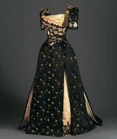Reception Dress (Bodice and Skirt), c.1890 This reception dress reflects the shift in interest from the enormous bustle of the mid-1880s to the oversized sleeves of the mid-1890s. The exaggerated sleeve counterbalanced the widening shape of the skirt, with the result that the waist of the hourglass silhouette seemed even smaller. The bold, dramatic color scheme and the combination of materials are typical of late-nineteenth-century styles. Overlapping panels on the asymmetrically draped…