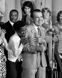 """During a live television broadcast from a youth rally at the GOP convention in Miami Beach, Richard Nixon finds himself on the receiving end of an enthusiastic embrace from entertainer Sammy Davis Jr., who calls Nixon """"the president and the future president of the United States of America."""" 1972."""