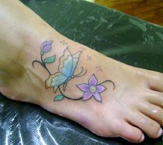 A butterfly with daisy flower tattoo on a foot.