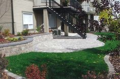 This small sloped city property has been tamed with a retaining wall, patio, and bridge edging.