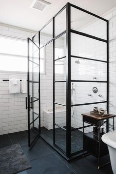 Industrial bathroom features a corner glass and shower enclosure filled with long white stacked tiles lined with small shower bench over a black grid shower floor.