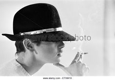 Model Twiggy posing in the studio wearing a black hat and smoking a cigarette. December 1966. - Stock Image
