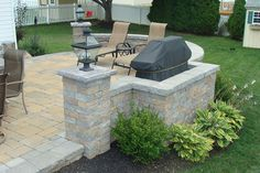 This patio is the perfect spot to cook up some bbq! Green Acres Nursery & Garden Center updated this patio with Cambridge Pavingstones and Wallstones. Cambridge Pavers, Paving Stones, Outdoor Living, Outdoor Decor, Landscape Walls, Wall Colors, House Design, Gallery, Garden