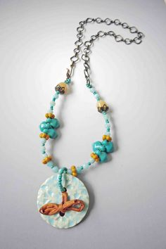 This turquoise colored amazonite necklace features semi-precious stones, vintage glass beads and an accent of gold silk. The beautiful, handmade ceramic pendant is patterned, and glazed on both side. I tied a bit of sari silk through the center of the pendant to pick up the color of the pretty gold colored, vintage glass beads.