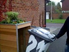 The garbage can is easily removed from its hiding place inside the full size Wheelie Bin Cover prototpe. Nick Staley's invention disguises trash cans as a planter with lovely flowers on top