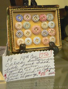 framed display of antique calico buttons (and check out the description on the tag!)