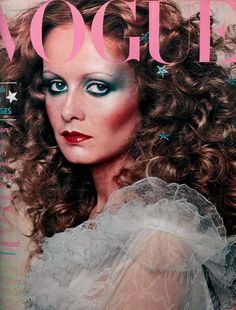 December 1974 Twiggy as Vogue's Cinderella in Zandra Rhodes' white silky chiffon and net, ruffles edged with turquoise thread, little flowers sprinkling the skirt; to order at Fortnum & Mason. Golden necklet, by Mick Milligan, at Liberty. Hair by Celine, highlights by Daniel. The stars, £1.59 to order, at Leonard. Make-up by Barbara Daly, using Estée Lauder. Scent - Alliage. Photograph by Barry Lategan