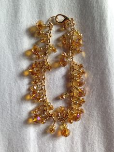 Clear yellow/gold glass beaded charm bracelet on gold chain!   Price: £8  Warning: Please keep this bracelet dry at all times! Do not wear it in the shower or continuous water use!