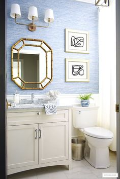 Coastal-Chic bathroom decor with a white vanity, regency style mirror, brass lighting and blue grasscloth wallpaper. #bathroom #bathroomdecor #blueandwhitedecor #abstractart #DIYart #smallbathroom #costalbathroom #coastaldecor #bathroomvanity #grasscloth #blueandwhite Costal Bathroom, Small Bathroom, Romantic Home Decor, Natural Home Decor, Retro Home Decor, Cheap Home Decor, Luxury Homes Interior, Home Interior Design, Bathroom Lighting Design