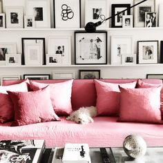 Pink couch, black and white frames.