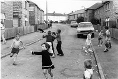 things in this photo you don't see anymore. Kids playing outside A road with minimum cars A dog crapping white poo""