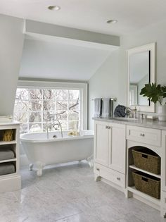 Molly Frey Design    Beautiful bathroom with sloped ceiling, soft aloe green walls paint color , white bathroom vanity, white carrara marble counter tops, marble tiles floor, vintage clawfoot tub and recessed hotel medicine cabinet mirror.
