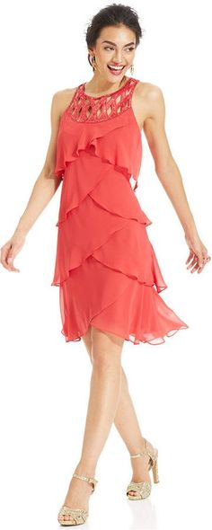 Un vestido corto para las fiestas con capas de tela en forma de pétalos y sin mangas. Elige unas sandalias con bling en dorado.