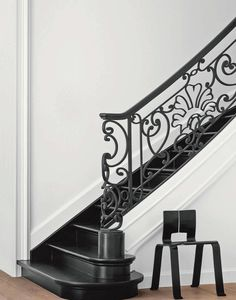 Under the staircase, Perriand's Ombre chair of black bent plywood creates an stark connection with the black iron baluster. Black Staircase, Staircase Railings, Staircase Design, Stairways, Banisters, Stair Treads, Iron Balusters, Marie Claire, Interior Inspiration
