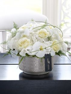 Featuring white snowball hydrangea, white Cambridge phalaenopsis orchid stems and white avalanche large headed roses with flexi grass and asparagus fern, expertly arranged in a gold ceramic planter and finished with luxury gold and black gift wrapping by Flowers.ie for maximum impact when your gift is delivered. Order Flowers ireland