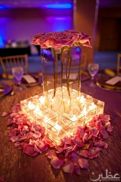 like the idea of the square votives around a square vase put not digging the roses i think layers of roses inside the square vase.