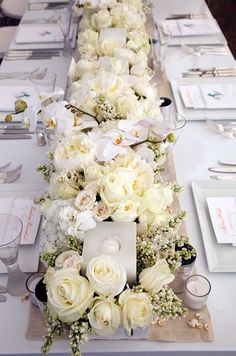I love the all white flowers! A long table is topped with white roses, orchids, and hydrangeas and accented with tiny seashells.