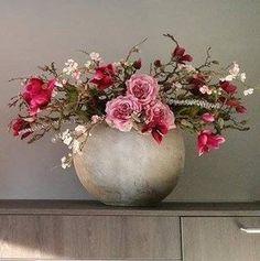 Decoratietakken met zijde <mark>bloemen</mark> in een betonnen pot