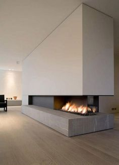 Minimalist Linear Fireplace with stunning details: Stone hearth, reveal at floor, blackened steel, cantilever.