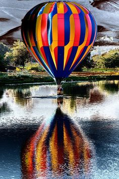 A colorful balloon reflects on a lake as it skims its surface
