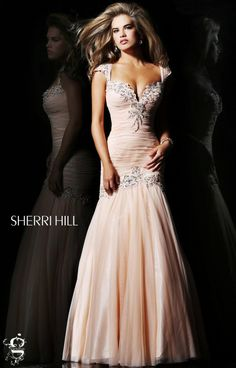 Sherri Hill 21069 is tres chic! This dress has a deep sweetheart neckline with cap sleeves in a fine luxurious embroidery. The gathered fabric on the drop waist bodice gives an alluring effect on those dangerous curves. The bodice is also trimmed with the beautiful embroidery in floral designs. The tulle skirt is flowy and sophisticated. Be effortlessly chic in this gorgeous dress!