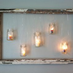Old window with hanging mason jars and candles. I love the potential versatility of these--change the color/scent of the candles to match the season...add bows to the frame or the mason jars, etc.