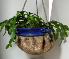 """Expressing the """"clothiness"""" of clay, this signature piece is what I call the """"gathered planter"""". A wheel-thrown rim holds the gathered lace impressed slab of clay in a form of contrasting color and texture. Approximately 8"""" wide and 6""""deep it will comfortably hold most outdoor and indoor plants. It does not have drain holes so that it is safe for indoor use. Plants may be placed directly in the pot as the wide rim provides aeration if not overwatered. The hanging rope is composed of moisture…"""