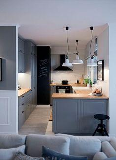 Półotwarta na salon kuchnia bazuje na zabudowie o barwie szarego błękitu. Nadmorską kolorystykę przełamują czarne dodatki, jak stołek czy okap albo farba tablicowa, którą wymalowano fragment ściany.
