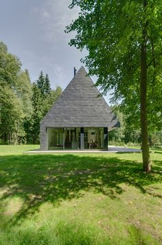 The upper storey of this home in the Lithuanian countryside is contained within a pointy shale-clad roof