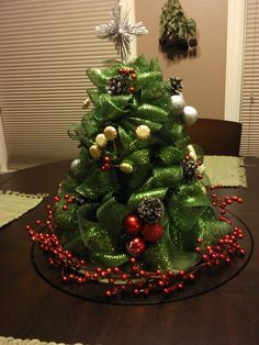 "Mesh Christmas Tree So while i was at my sisters house during Thanksgiving we did so much fun stuff! Here is one of the crafts i got to help her with! Isn't this tree a cutie? And it's the perfect size for the middle of her kitchen table - on the lazy Susan....i LOVE lazy Susan's especially on kitchen tables ;) So would you like to make one? Here's how we made hers! These are the only 3 things you'll need (and decorations...if you want) The Mesh Ribbon we used was 2 1/2"" wid"