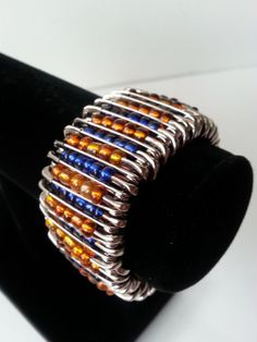 Safety pin bracelet in Denver Bronco colors Safety Pin Bracelet, Safety Pin Jewelry, Safety Pins, Denver Broncos Colors, Go Broncos, Jewelry Crafts, Jewelry Ideas, Jewelry Design, Beaded Braclets