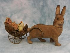 """Antique glass eyed paper mache Rabbit candy container pulling a cart is 11"""" long from front to back. The cart attaches to the rabbit by the bent wood hooked into wires on both sides of the rabbit. The moss and reed cart has wheels of antique pot metal. The Rabbit stands 7"""" tall up to the top of his ears, head is removable to put candy inside. The 4"""" doll in the cart is attached. She is all wax with black painted stocking, molded shoes and factory original clothing. She has a straight leg…"""