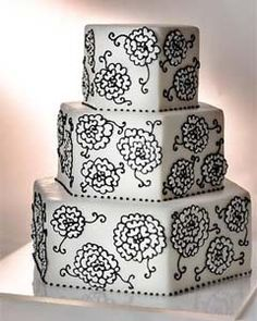 Three tier hexagon shaped black and white wedding cake, decorated with intricate black embroidery patterns