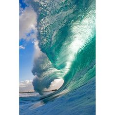 A large, backlit wave throws out a crest as it approaches the shore in Oahu, Hawaii. The foam seen on the water surface is left over from the explosion of the previous wave breaking.