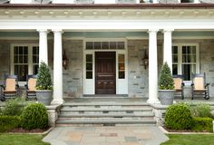 Love this Front Porch!  Bluestone pavers, oak stained front door, ceiling painted Benjamin Moore 1619 Silver Mist, gas lanterns by Bevolo, bluestone on the walls, Jeldwen wood windows, black rocking chairs, large gray pots with topiary