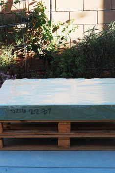 High density foam cut to fit on top of pallet. Cover in outdoor vinyl. to waterproof. Next: removable cushion covers.