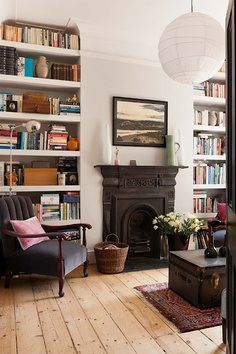 bookshelves around fireplace, fire, interior, home, armchair, wooden floors, paper lampshade, books, home, living room