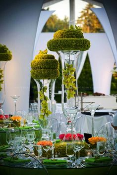 Decor of Green, green cymbidium orchids hang from green button chrysanthemum covered wreaths above and below with colored roses scattered over the table