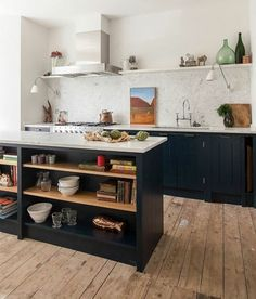 This is a galley kitchen with an island with exposed shelves.