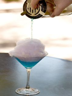 Cotton Candy Martini Recipe: Pinnacle cotton candy flavor vodka, 2 oz Blue Curacao liqueur Grenadine, a splash Pineapple juice a splash Champagne, a splash Cotton candy, a generous chunk Crushed ice Sugar for rim