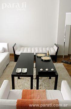 El living se armó en torno a dos mesas ratonas gemelas de wengué ($ 790, Astromelia). A su alrededor, una banqueta con tapizado capitoné de gabardina y estructura de wengué ($ 1.430, Astromelia) corta la rigidez del conjunto de sofá y sillón con forma de cubo y funda de gabardina blanca ($ 2.750 y $ 1.100, Astromelia). El toque de color lo da la manta tejida ($ 215, Flox). La alfombra de pelo blanco (desde $ 400, Americana) le da un cierre al grupo.