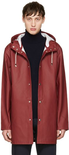Long sleeve rubberized cotton raincoat in burgundy. Water resistant. Double welded seam construction. Cotton drawstring in off-white at hood. Press-stud closure at front. Welt pockets at waist. Logo embossed at front hem. Eyelet vents at armscyes. Bonded lining in white. Silver-tone hardware. Tonal stitching.