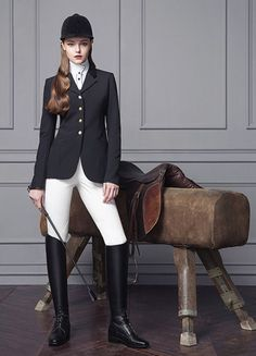 Anastasia Milli posing with pommel horse and English riding saddle - black coat white breeches leather boots and helmet crop 2020-05-31