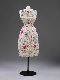 Evening dress, 1962 Short evening dress of white wild silk, with hand embroidered coloured floral motifs in the Chinese style. It is fitted and has a wide round neck, slightly lower at the back. It is sleeveless and has a side zip fastening. The dress is fully lined with white silk.