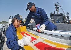 YOKOSUKA,Japan(April 16, 2013)Aviation Boatswain's Mate(Handling)Airman Recruit Nichole Robinson,from Chicago,left,& Aviation Boatswain's Mate(Handling)Airman Recruit Nefetari Brooks,from Miami,paint bomb jettison ramps on flight deck of carrier USS George Washington(CVN 73).George Washington & embarked air wing,Carrier Air Wing(CVW)5,provide a combat-ready force that protects & defends collective maritime interest of US & allies & partners in Indo-Asia-Pacific region.
