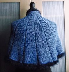 This crescent shaped shawl uses garter short rows for shaping, with a band of stocking stitch between sections. A faux fur edging gives the garment a feel of luxury.