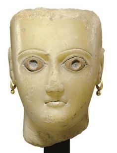 """A SOUTH ARABIAN ALABASTER FEMALE HEAD CIRCA 1ST CENTURY B.C.-1ST CENTURY A.D. The spade-shaped face with small fleshy lips and a triangular nose, the thin grooved brows arching over the almond-shaped eyes, the sclerae inlaid in limestone, additional inlays for the pupils now missing, the top and back of the head flat and roughly finished, the ears pierced, wearing ancient gold hoop earrings, possibly original, """"Venus""""-lines along the neck"""